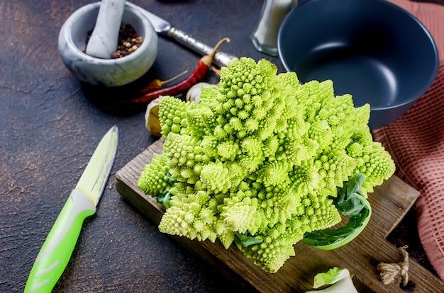 Romanesco vert frais, chou biologique cru prêt pour la cuisson sur une planche à découper