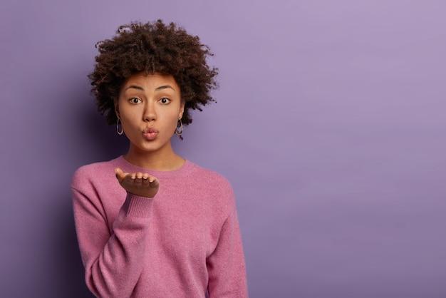 Romantique belle femme aux cheveux afro envoie un baiser d'air sensuel de la paume ouverte
