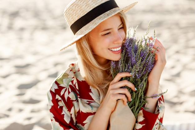 Romantique heureux gros plan portrait de charmante fille blonde au chapeau de paille sent les fleurs sur la plage du soir, couleurs chaudes du coucher du soleil. bouquet de lavande.