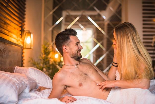 Romantique heureux jeune couple sur le lit