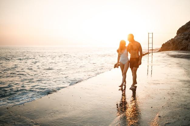 Romantique jeune couple amoureux marchant ensemble au coucher du soleil le long de la plage méditerranéenne. vacances d'été dans un pays chaud. heureux couple marié en vacances en turquie. mise au point sélective