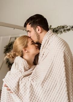 Romantique jeune couple recouvert d'une couverture