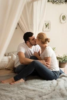 Romantique jeune couple s'embrassant à la maison