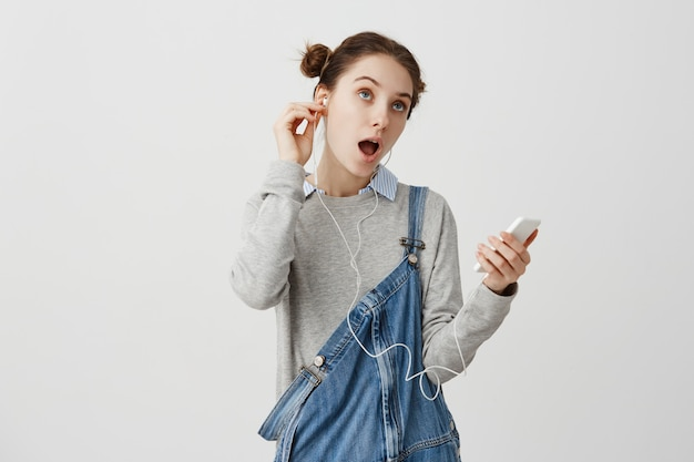 Romantique jeune femme aux cheveux en double chignon chantant tout en profitant de la musique de son téléphone portable. amateur de musique féminine au repos après une dure journée d'écoute de chansons à l'aide d'écouteurs. concept de passe-temps