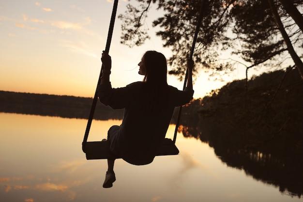 Romantique jeune femme sur une balançoire sur le lac au coucher du soleil. voyageur jeune fille assise sur la balançoire dans la belle nature, vue sur le lac