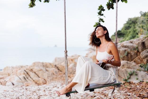 Romantique jeune femme caucasienne calme heureux avec ukulélé sur la plage rocheuse tropicale au coucher du soleil