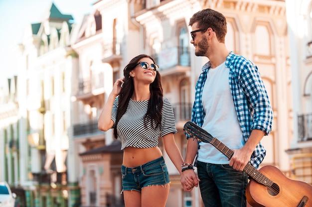 Romantique de la ville. souriant jeune couple d'amoureux se tenant la main et se regardant en marchant le long de la rue