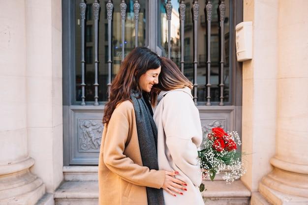 Romantiques jeunes copines avec des fleurs sur la rue
