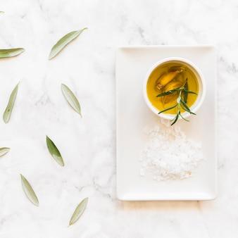 Romarin et ail gousses d'huile dans un bol avec du sel sur un plateau blanc