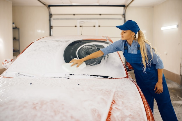 La rondelle femelle avec une éponge essuie le pare-brise de l'automobile