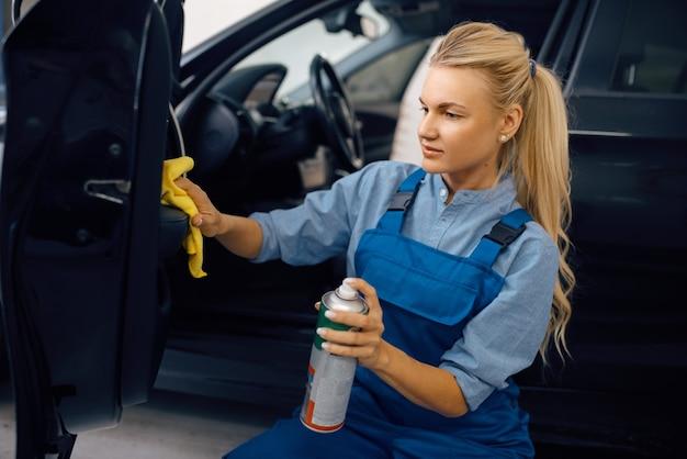 La rondelle femelle avec une éponge nettoie la garniture de porte automobile, le service de lavage de voiture femme lave un véhicule, station de lavage de voiture, entreprise de lavage de voiture