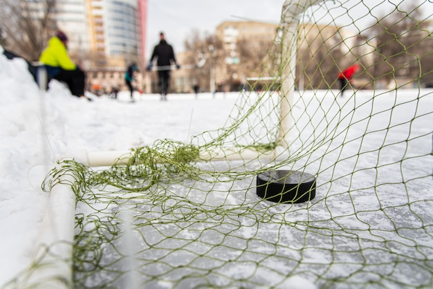 Rondelle de hockey dans le gros plan du filet de but