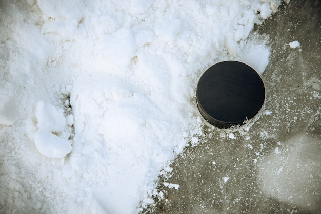 La rondelle de hockey noir se trouve sur la glace au stade