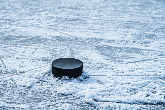 La rondelle de hockey se trouve sur le gros plan de la neige