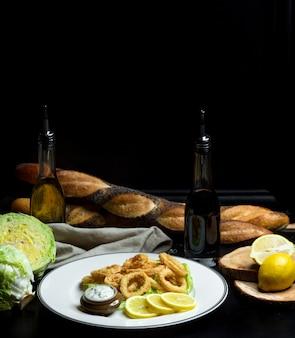 Rondelles d'oignon en pâte avec sauce et tranches de citron