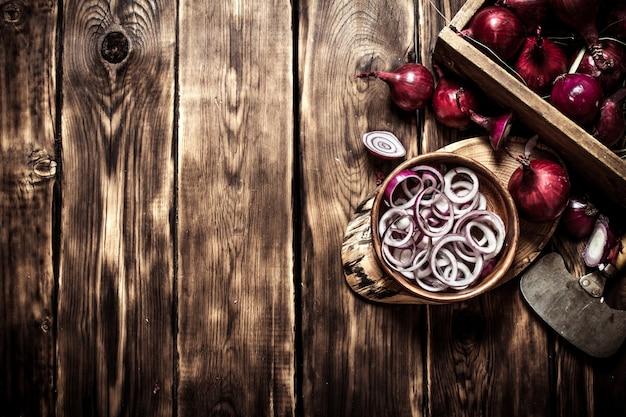 Rondelles d'oignon en tranches dans une tasse sur un tronc d'arbre sur une table en bois.