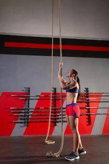 Rope climb exercice femme au gymnase