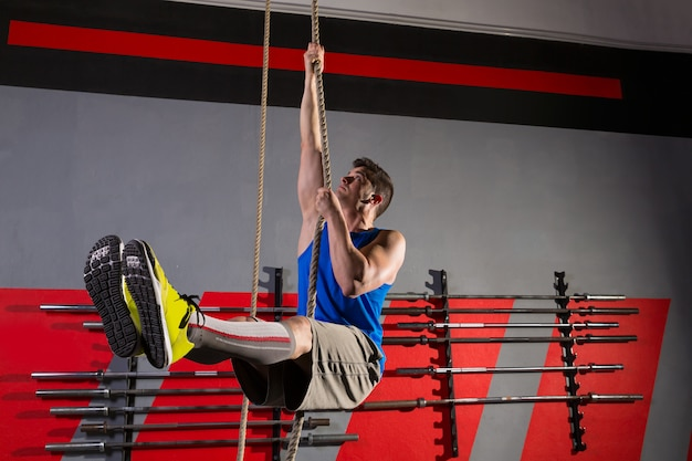 Rope climb exercice homme au gymnase