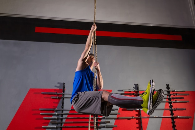 Rope climb exercice homme au gymnase