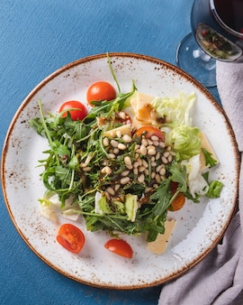 Roquette de salade verte, tomates cerises et pignons de pin. vue de dessus. fermer