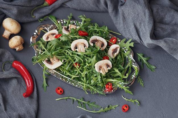 Roquette verte fraîche aux champignons et piment sur une plaque d'argent sur fond gris foncé. gros plan d'aliments sains verts frais.