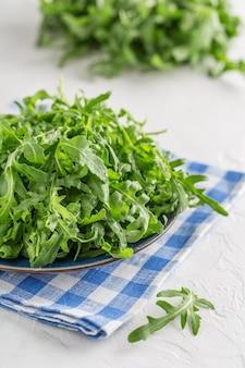 Roquette verte fraîche dans un bol sur la table. roquette pour salade
