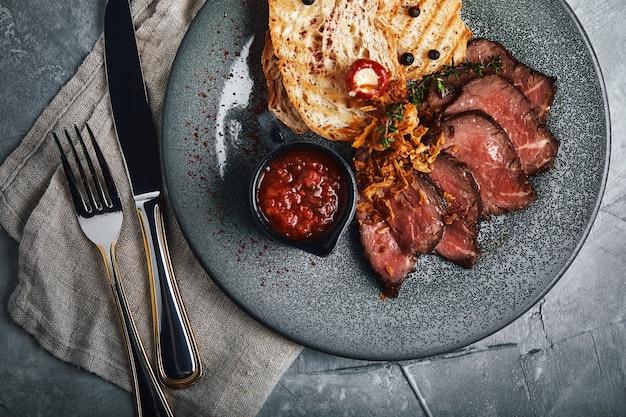 Le rosbif juteux avec ciabatta à la sauce tomate est joliment tranché et disposé sur des assiettes.