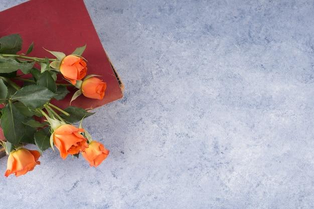 Rose bouquet et livre minable sur la table de grunge