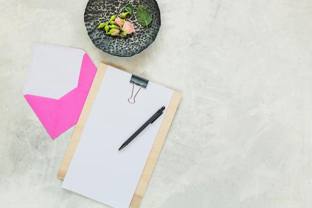 Rose et bourgeons sur le plateau en pierre avec enveloppe rose et stylo sur le presse-papiers
