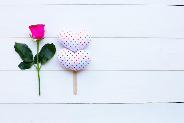 Rose et coeurs de la saint-valentin sur un fond en bois blanc.