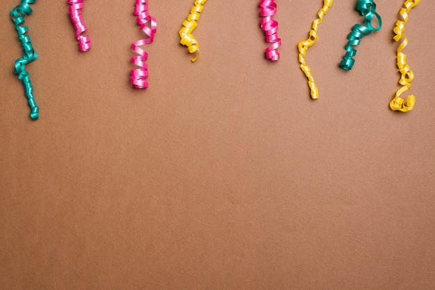 Rose coloré; streamers verts et jaunes sur fond marron