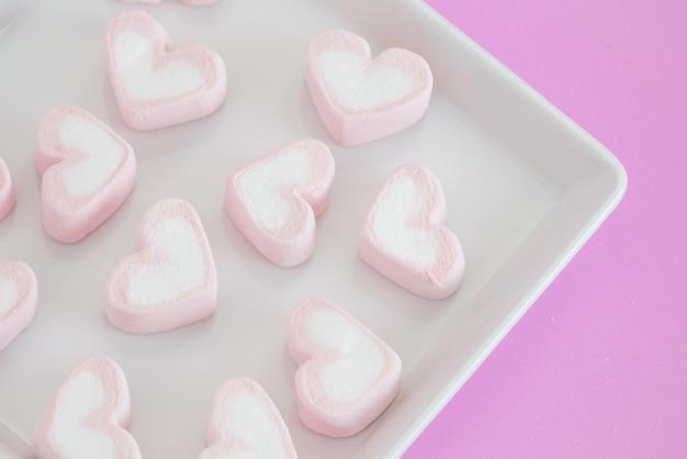 Rose entendre guimauve, bonbons coeurs de guimauve sur fond rose. cadeau saint valentin