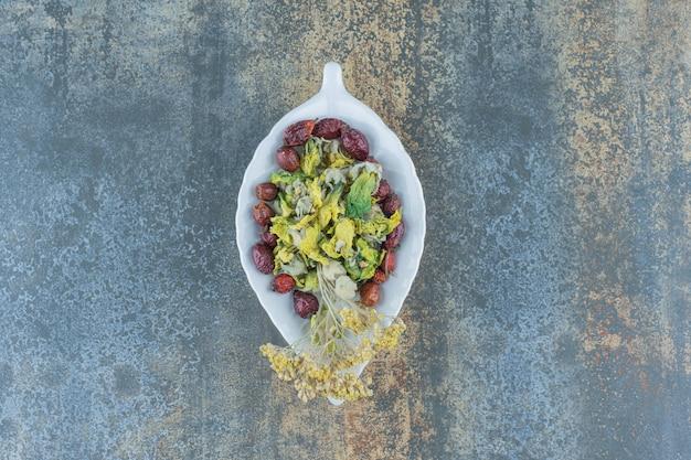 Rose et fleurs biologiques séchées sur une assiette en forme de feuille.