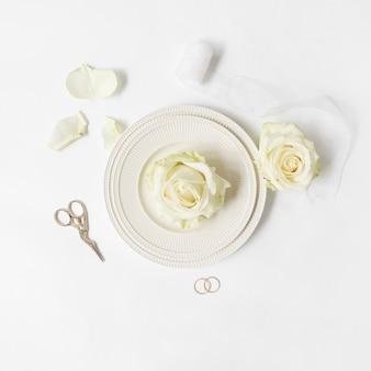 Rose fraîche sur une assiette avec un ruban; ciseaux et alliances sur fond blanc
