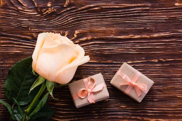 Rose fraîche et un couple de cadeaux emballés sur bois, vue de dessus