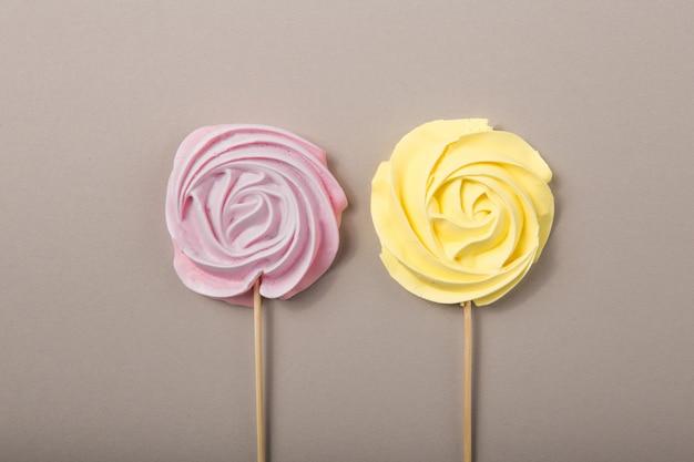 Rose, jaune rose bonbons aux couleurs pastel sur un bâton en bois sur fond gris, saint valentin, fête des mères.