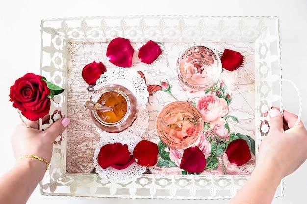 Rose limonade et confiture de rose sur un plateau. deux mains de femme tenant un plateau.