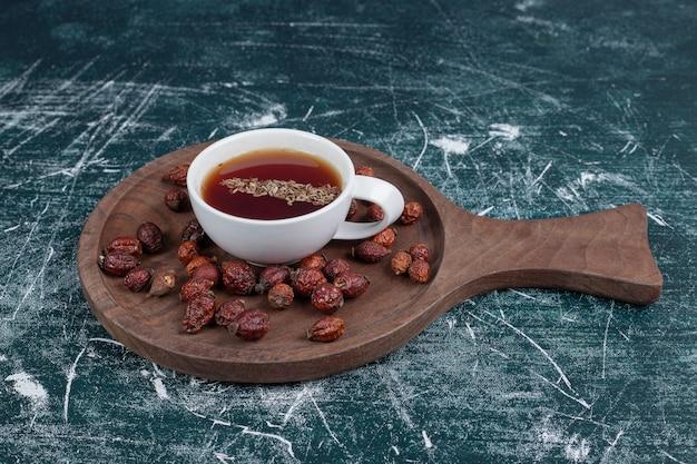 Rose musquée séchée et tasse de thé sur planche de bois. photo de haute qualité