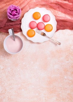 Rose pourpre; tasse dans le lait et les macarons sur une assiette en céramique avec une fourchette avec du lin textile sur fond texturé