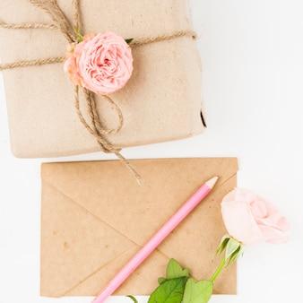 Rose rose; crayon sur enveloppe de papier brun et colis attachés avec des ficelles sur fond blanc