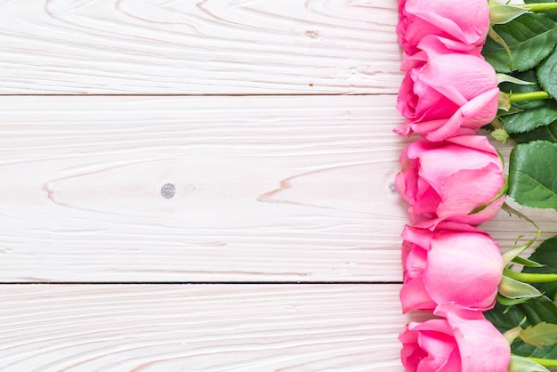 Rose rose dans un vase sur fond de bois