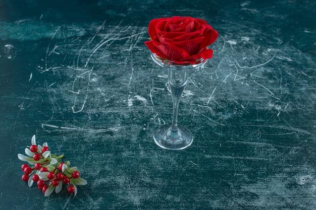 Rose rouge artificielle dans un socle en verre, sur fond bleu.