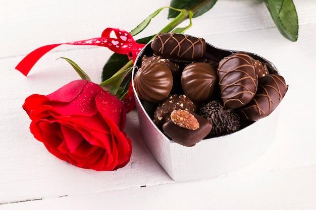 Rose rouge, boîte de chocolats sur un fond en bois blanc