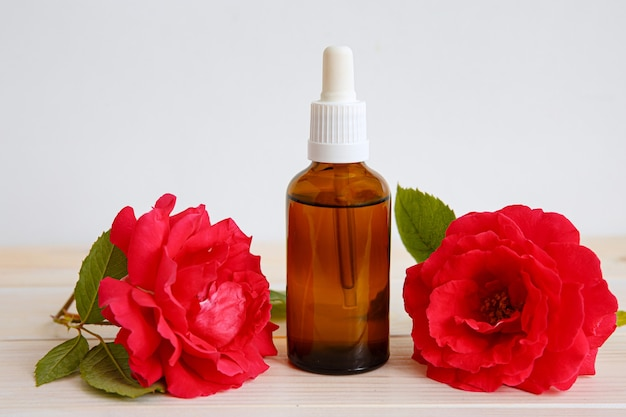 Rose rouge et bouteille avec de l'huile ou des médicaments aromatiques.