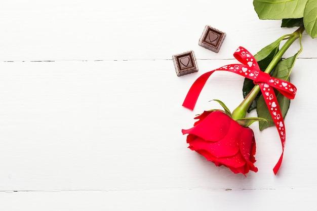 Rose rouge, chocolats sur fond de bois blanc