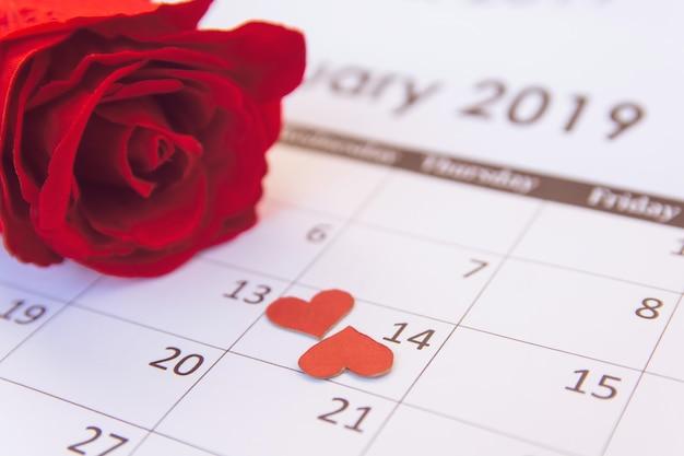 Rose rouge et coeurs rouges sur la page du calendrier