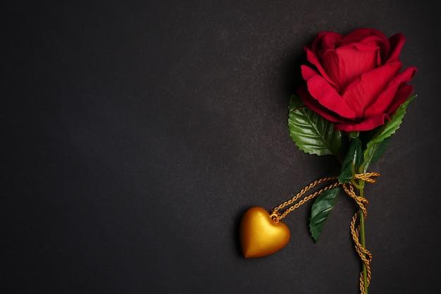 Rose rouge avec collier coeur or sur fond noir. concept de la saint-valentin. espace libre pour le texte