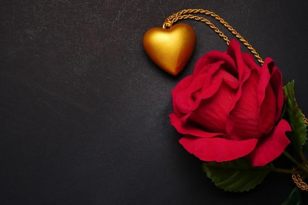 Rose rouge avec collier coeur or sur fond noir. concept de la saint-valentin.