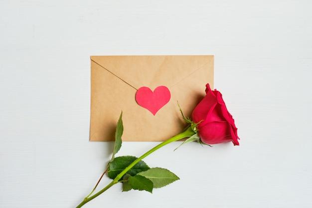 Rose rouge sur une enveloppe avec coeur vue de dessus.