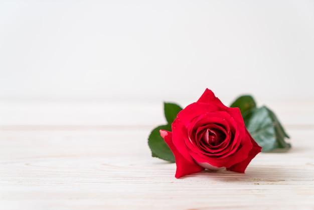 Rose rouge sur fond de bois avec fond